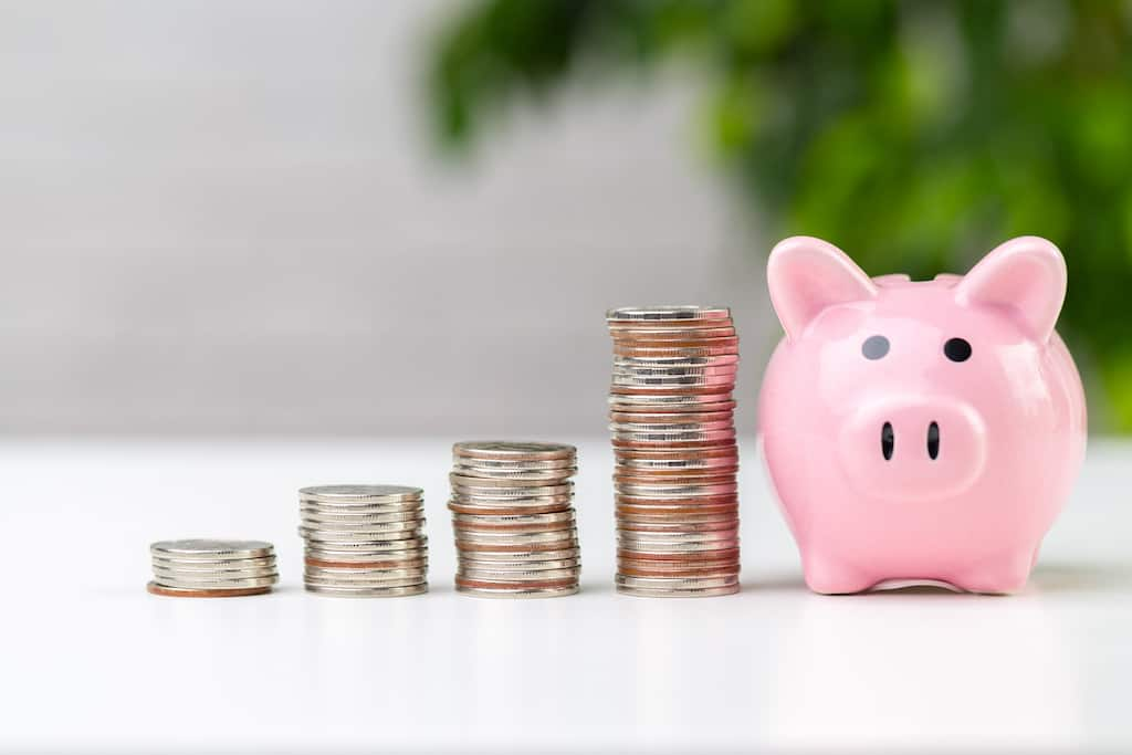 A piggy bank next to three stacks of coins on a table, representing reserve funding methods.